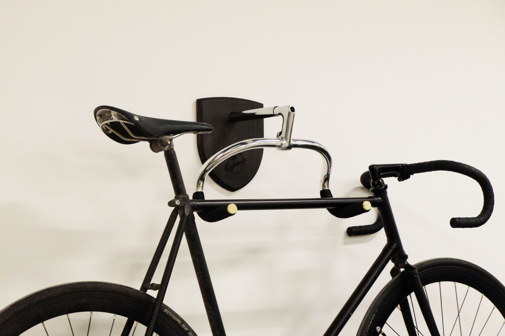 The Bike Hanger in black on a wall with a bicycle - KP Cykler